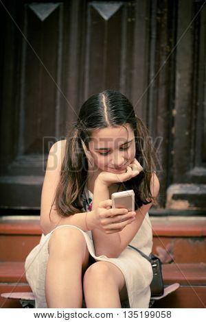 teen girl sit on stairs at street use her smart phone closeup
