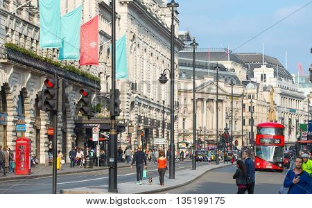 LONDON, UK - OCTOBER 4, 2015: Piccadilly street with lot of walking people, pedestrians and public transport, cars, taxis on the road.