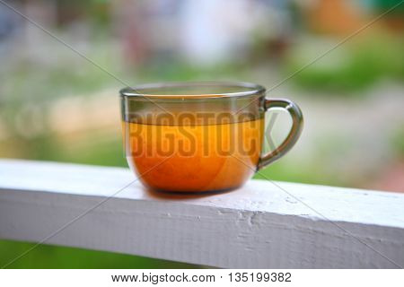 tea of sea buckthorn berries in a transparent Cup on the railing of the veranda