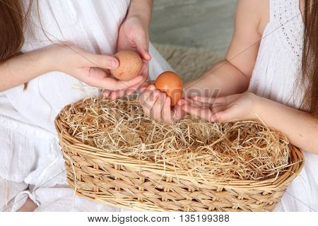 girl holding a chicken egg in the palms quail eggs in a simulated nest