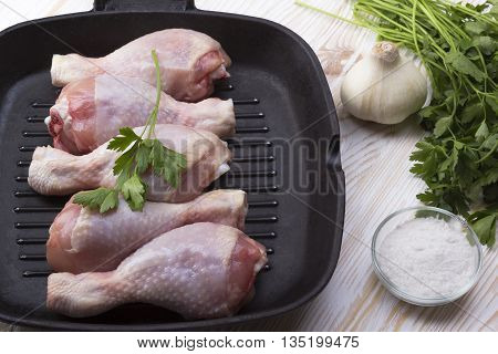 raw chicken drumstick in pan with salt, garlic, parsley on wooden table