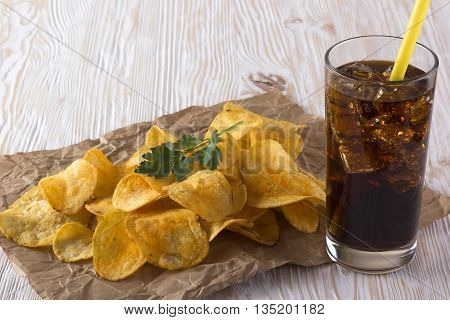 Potato chips with soda on wooden background