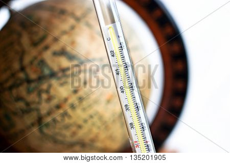 thermometer with antique globe on white background