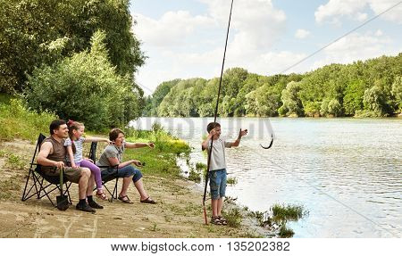 family camping and fishing, river and forest, summer season