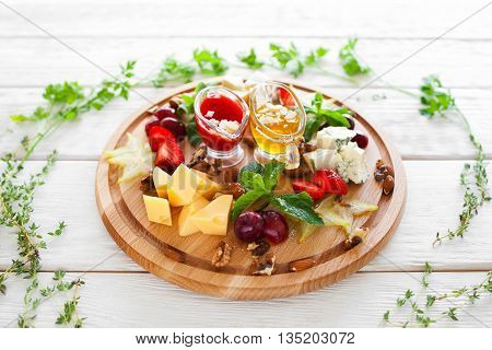 Plate with snacks for wine in herbal frame on white. Top view on few kinds of cheese and fruits on catering platter with red and yellow sauces. Wine snacks plate on white wooden background