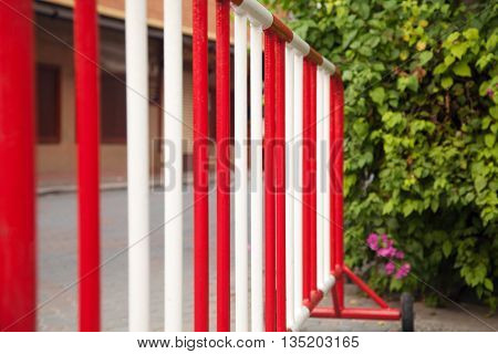 Metal red and white safety barrier on a road. Stop sign railing against green bushes