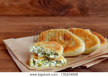 Fried pies stuffed with cheese, green onion and dill. Delicious homemade pies on paper and wooden background. Food idea for a summer picnic