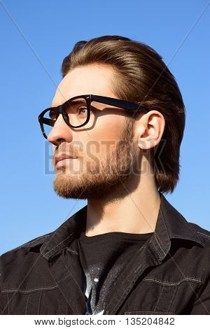 Handsome man in black jacket and spectacles posing outdoor over blue sky. Men's beauty, fashion. Business style.