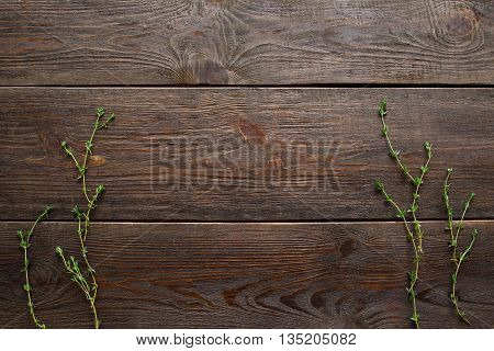 Rosemary herb on dark wood flat lay, copyspace. Top view on dark wooden background with rosemary brunches on both sides, void.Rosemary frame on wood