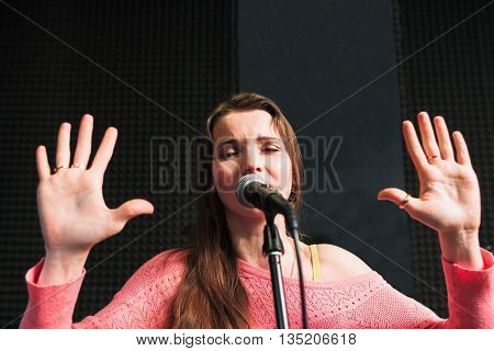 Emotionally singing young girl with closed eyes and raised palms. Protesting woman in pink dress near the microphone.
