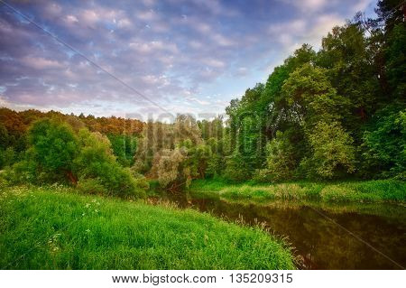 evening spring landscape with a dramatic sky and green meadow and river