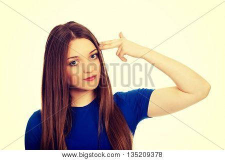 Despair teenage woman making gun sign.