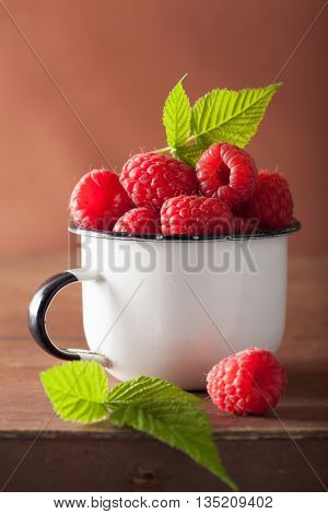 fresh raspberry in enamel cup over wooden background