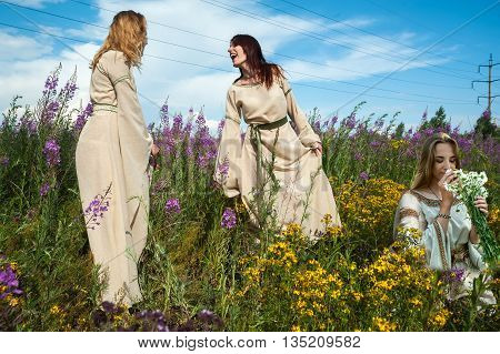 Attractive women in traditional russian clothes relaxing on fireweed meadow. Ivan Kupala Holiday Celebration