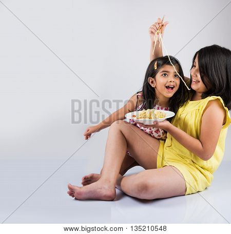 Happy Asian children eating delicious noodle, two cheerful little indian girls eating noodles in white dish isolated over white background