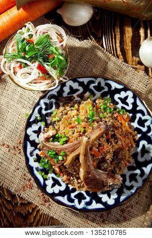 Pilaf - Rice with Lamb Chops and Vegetables. Garnished with Onions and Tomatoes Salad