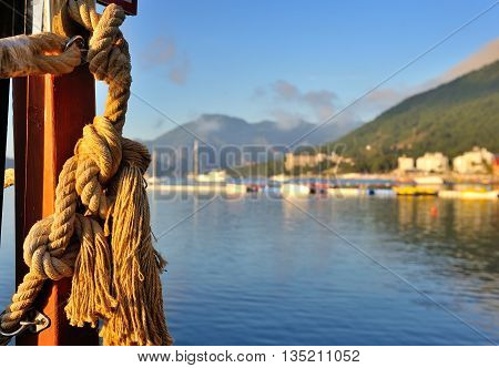 Rope with marine knots on the background of the coast with mountains