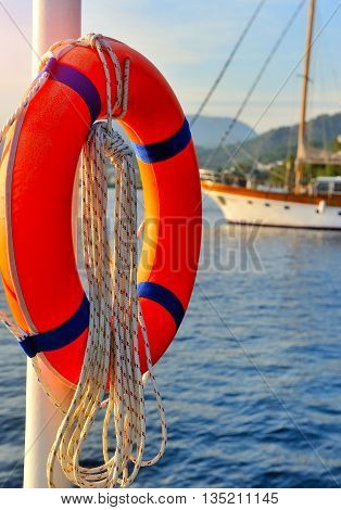 Orange lifebuoy against the backdrop of the sea and boats
