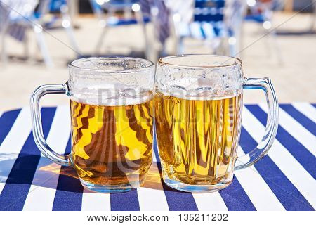 Two mugs of beer on a table in a cafe on a sunny day