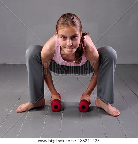 Teenager girl doing exercises with dumbbells to develop with dumbbells muscles on grey background. Sport healthy lifestyle concept. Full length portrait of teen child exercising with weights.