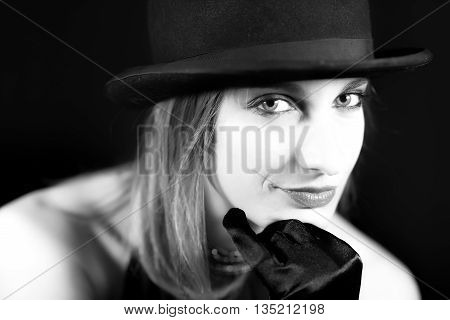 Portrait in black and white blond woman with bowler hat on a black background
