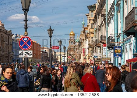 ST. PETERSBURG, RUSSIA - April 17, 2016: Many people, Tourists on Nevsky street, Church of the Saviour on Spilled Blood on Background, St. Petersburg, Russia