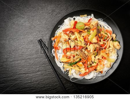 Rice noodles with vegetables, mushrooms, chicken and soy sauce.