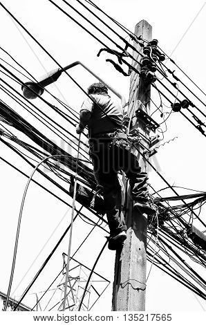 Black and White in Silhouette photo effect. Electricians repairing wire at climbing work on electric post power pole