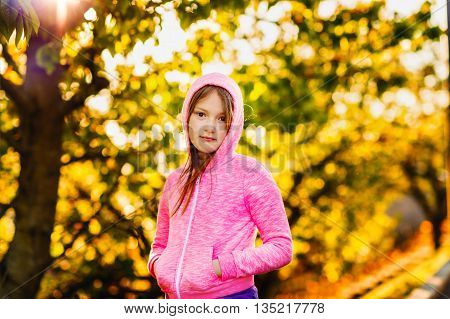 Outdoor portrait of a cute little girl of 8-9 years old at sunset, wearing bright pink hoody