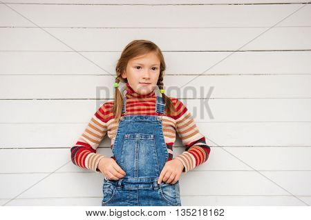 Fashion portrait of a cute little girl against white background, wearing stripe roll neck pullover and denim overalls