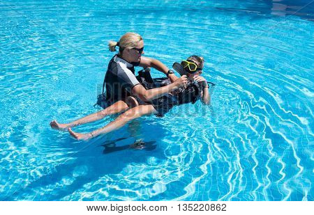 PaliouriGreece - June 15 2016: Young woman tries a scuba dive in a pool with an instructor.Scuba diving is a fun sport enjoyed by many people.