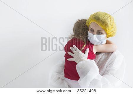 Woman in white uniform hugs little girl