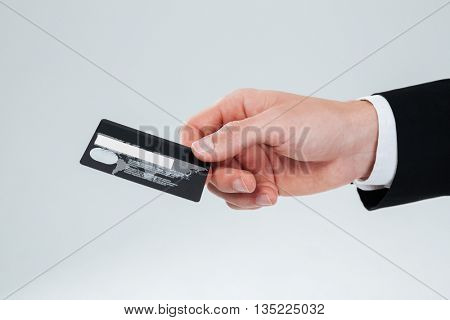 Closeup of hand of businessman holding credit card over white background