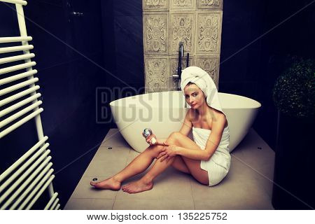 Woman with cosmetic cream in bathroom.