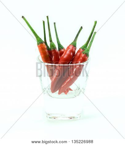 group of chilli peppers in glass cup on white background isolated
