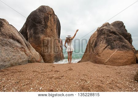 Lonely slender woman on a deserted beach on the background of large stones and a cloudy sky. She is facing to sea and waves her hand.