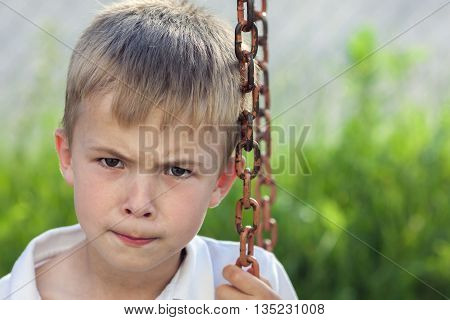 Portrait of a little displeased and dissatisfied boy with golden blonde straw hair in sunny summer day on green blurred background