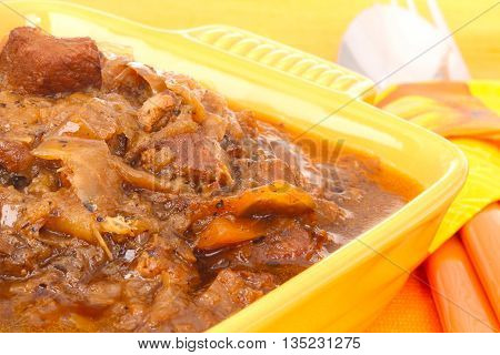 cabbage goulash with cutlery in yellow cup