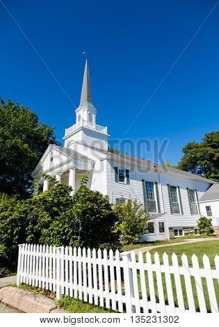 White Church Beyond Picket Fence under blue sky