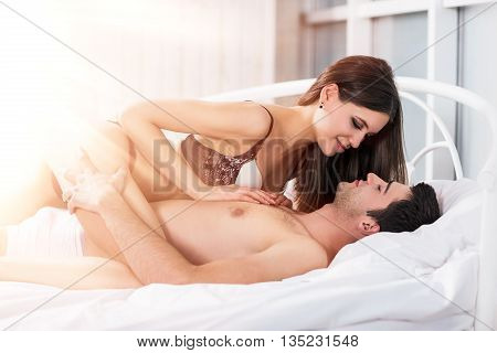 Young passionate couple lying in bed and bright sunlight shining from window