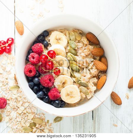 Healthy breakfast. Oatmeal porridge banana raspberries blueberries red currants pumpkin seeds and almonds in a bowl on white background.