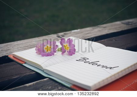 Beloved text on open notebook with flower on wooden table