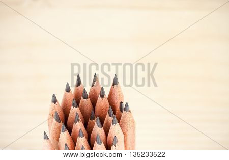 Bunch of wooden cheap sharp pencils shot on wooden background as macro close-up shot