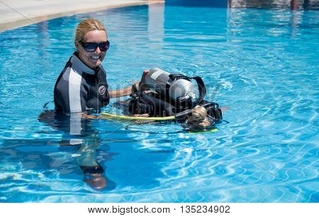 PaliouriGreece - June 15 2016:Young woman tries a scuba dive in a pool with an instructor.Scuba diving is a fun sport enjoyed by many people.Photographs taken in an open pool with no photography restrictions