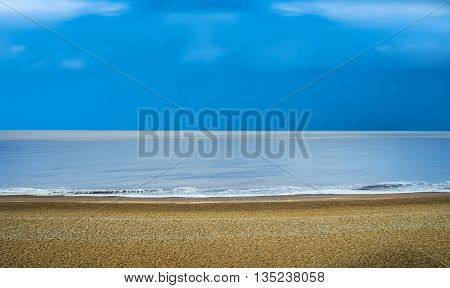 Sandy beach backdrop with calm water and blue sky tropical holiday concept panoramic view