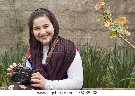 Smiling Young Little Girl Is Strapped an Analogue Camera on Her Neck in Flower Garden