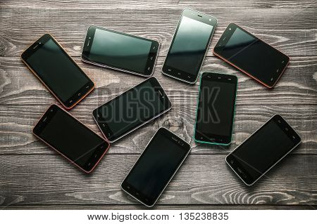bunch of smart phones on wooden rustic background
