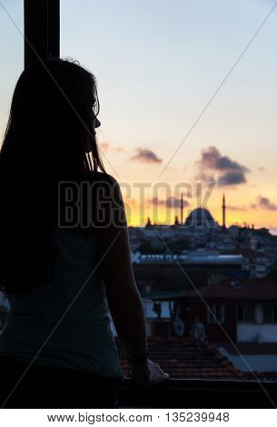ISTANBUL, TURKEY - JUNE 19, 2015: Silhouette of young woman looking at Istanbul on sunset Turkey