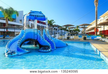 Space by pool with sun loungers childrens playground with slides