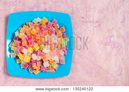 Colorful candy and jelly in color dish on pink background